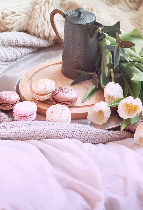 peaceful life illustration with cocoa and macaroons on bed
