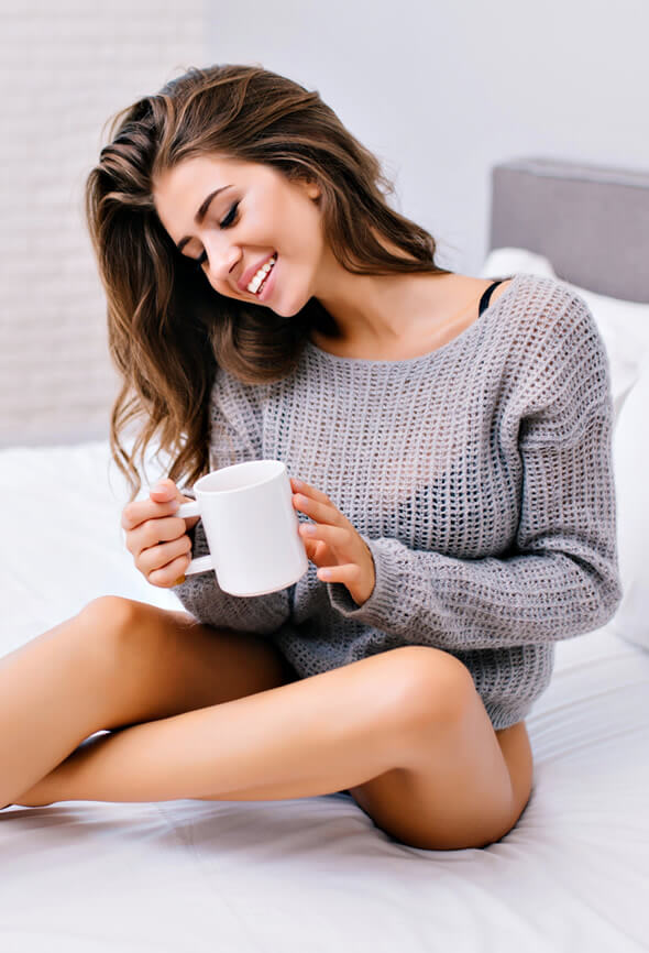 pretty woman with atelophobia sitting on the bed smiling