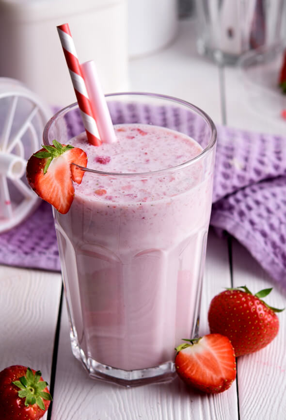 protein shake with strawberries and a straw