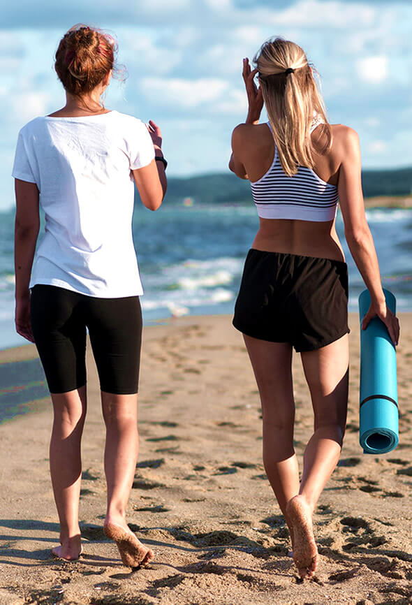 two women on the beach doing a walking challenge