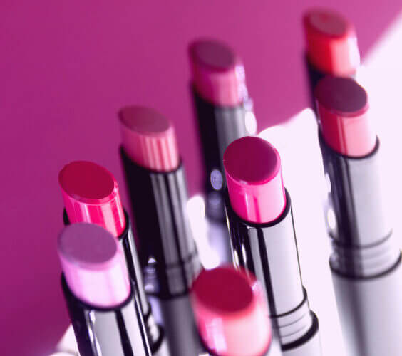 various lipstick shades on a pink background