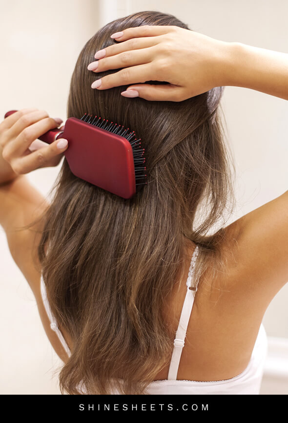 woman brushing healthy hair after doing beauty habits for hair improvement