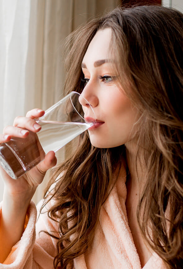 woman drinking water to look well rested
