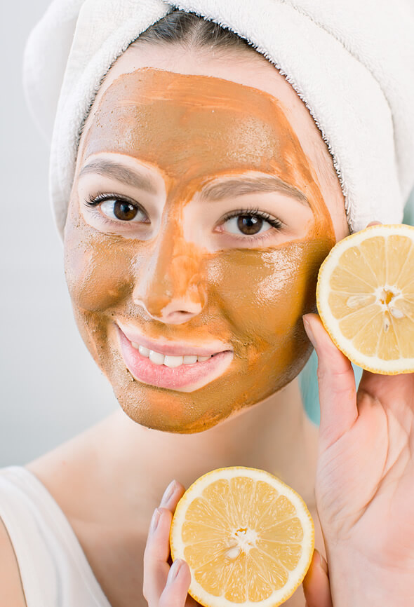 young woman using lemon pumpkin enzyme peel on her face