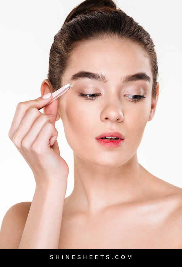 woman performing eyebrow plucking as part of her beauty habits