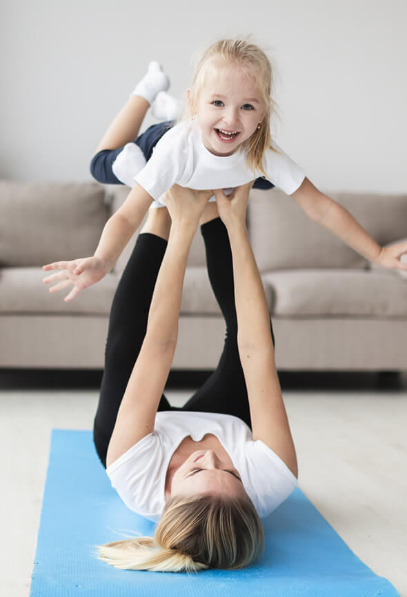 woman playing with her child on yoga mat as part of her active lifestyle