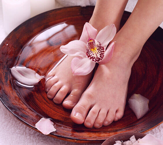 feet in a foot spa bath with flowers
