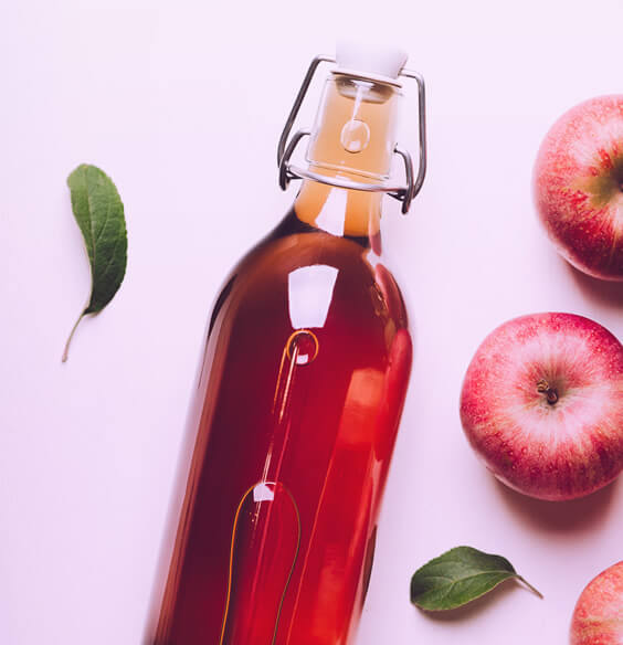 apple cider vinegar for hair rinse and apples on the table