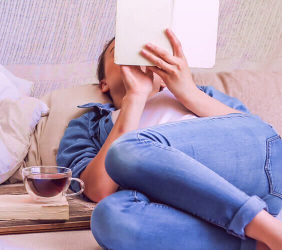 woman laying on the bed and writing in a journal