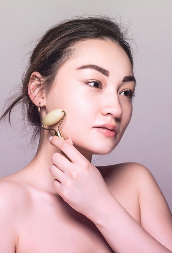 woman giving herself a gua sha massage