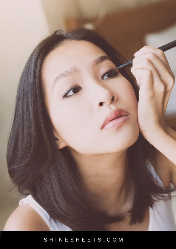 young asian woman applying makeup on her hooded eyes