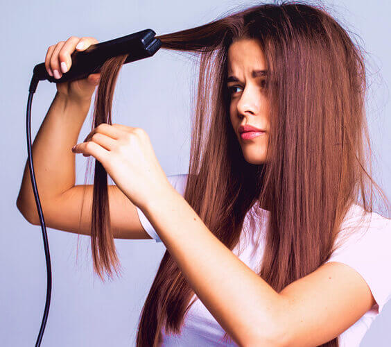 woman trying to straighten her frizzy hair with a flat iron