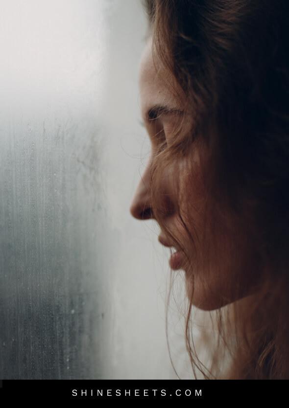 sad woman looking through the window into the rain