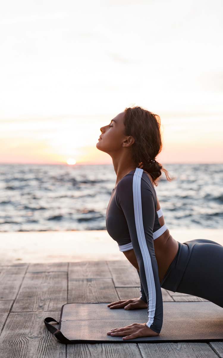 woman in the beach doing stretching exercises