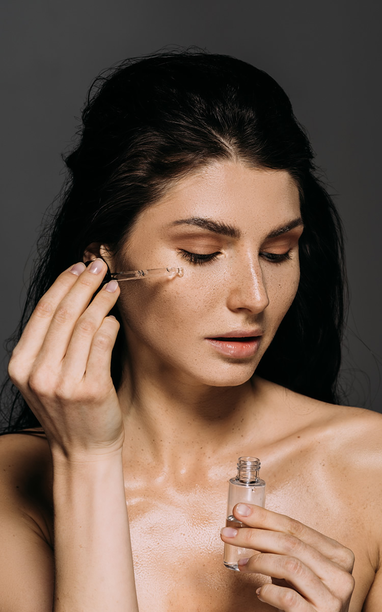 woman using serum for agging skin on face