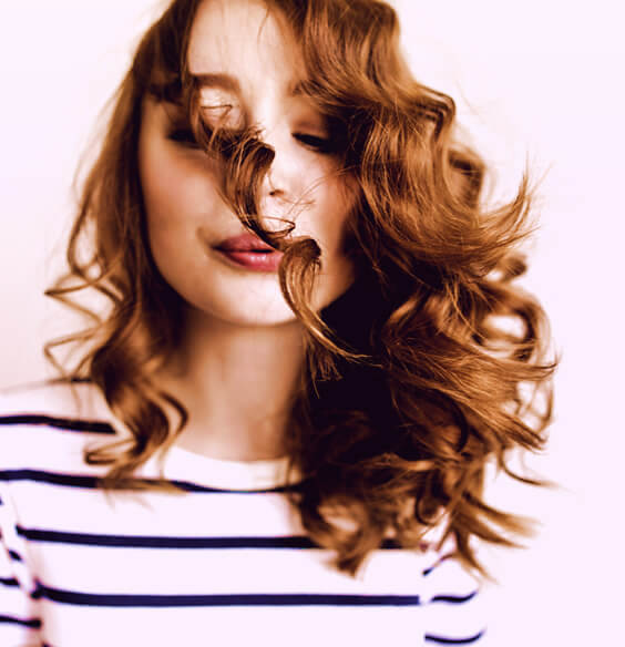 woman with perfect hair health and bouncy red curls