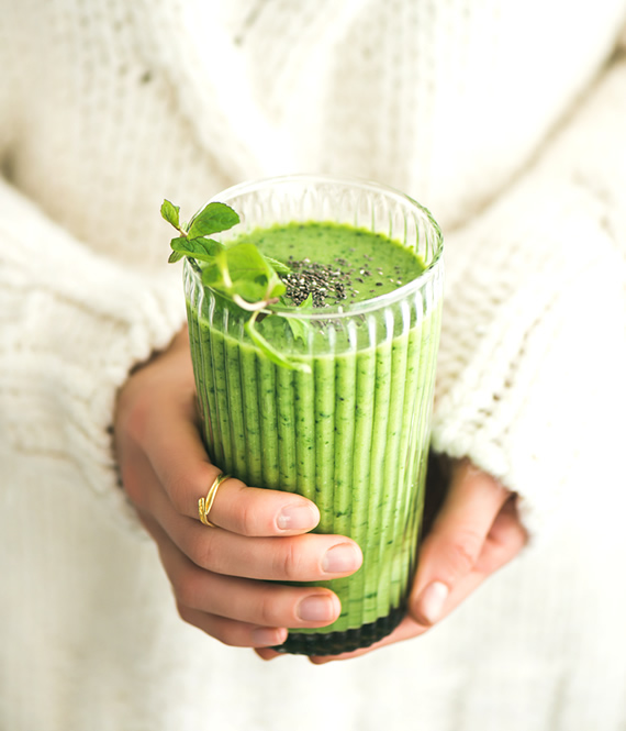 girl with orthorexia holding a green drink in her hands