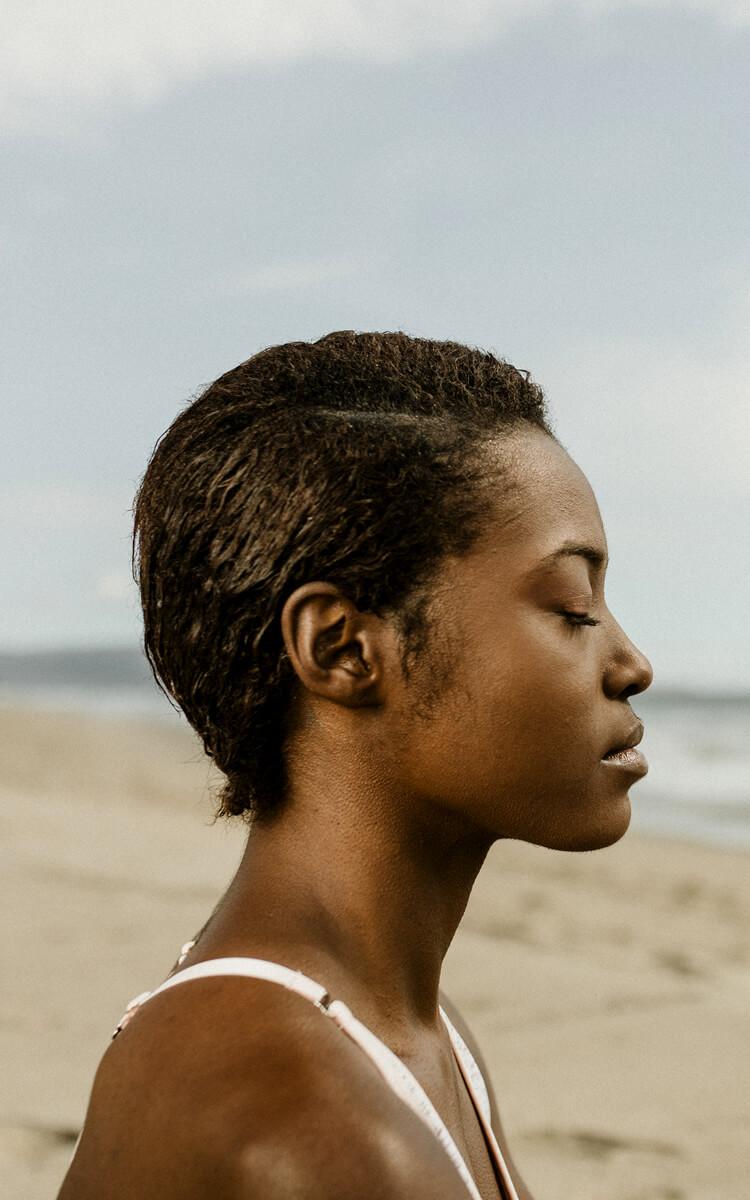 pretty black woman meditating to overcome self-destructive behavior