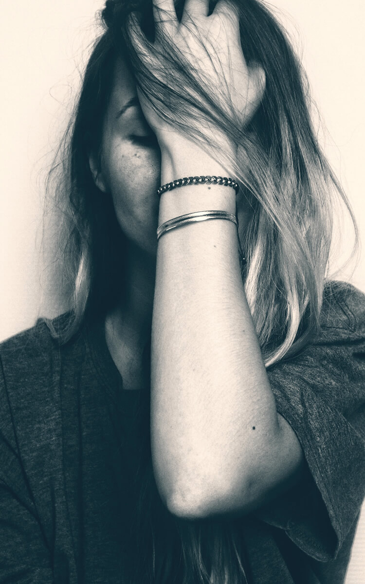 woman feeling sad emotions that trigger self-destructive behavior