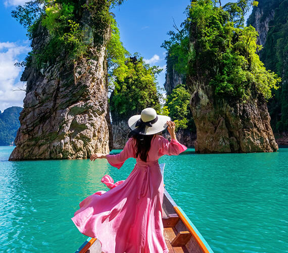 woman with a hat and pink dress near water body