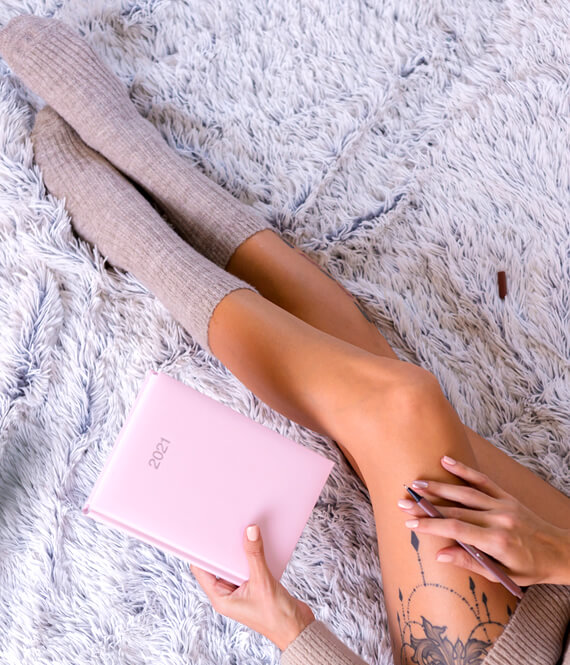 woman with long socks holding journal planner notebook