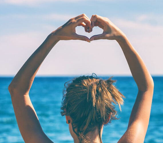 woman doing heart shape with hands as symbol of learning to love yourself