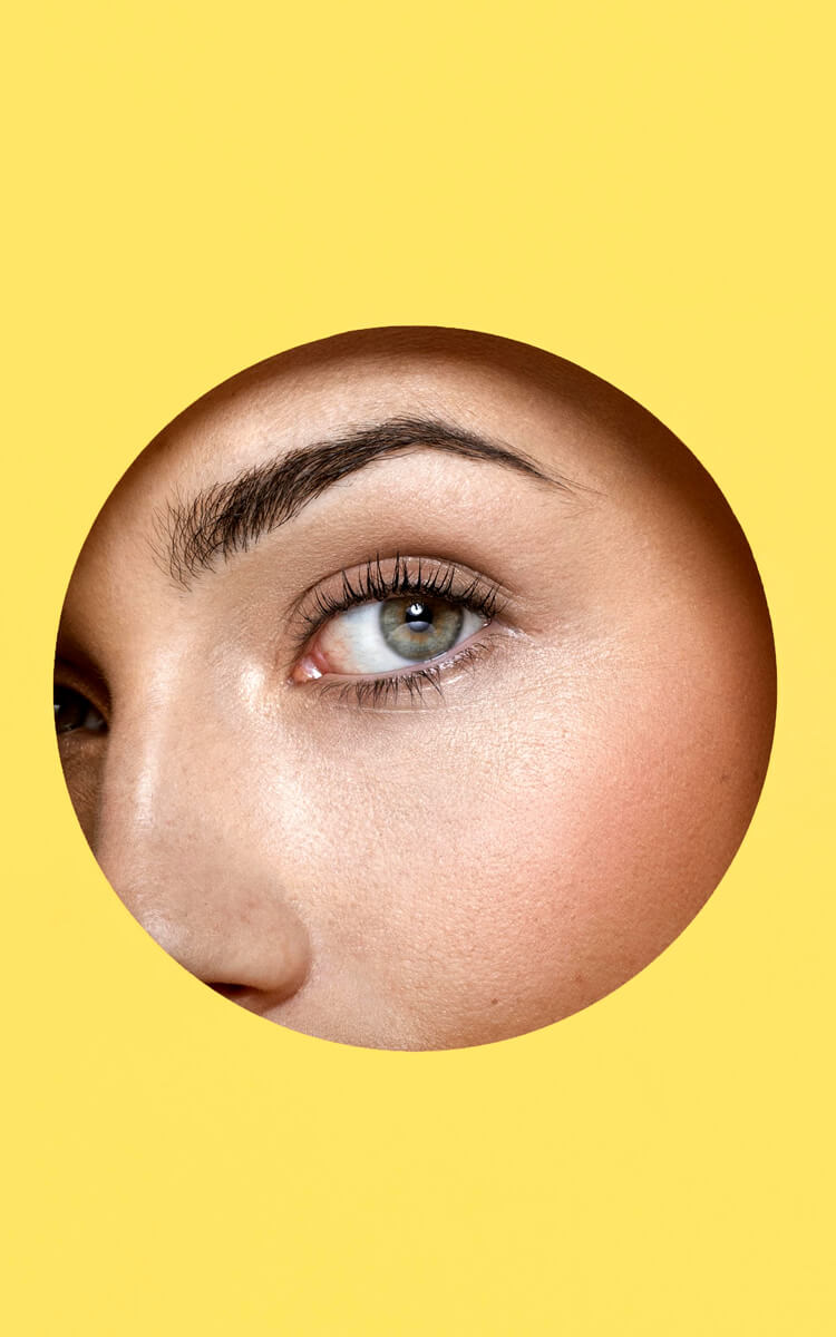 woman eye through a hole in yellow paper