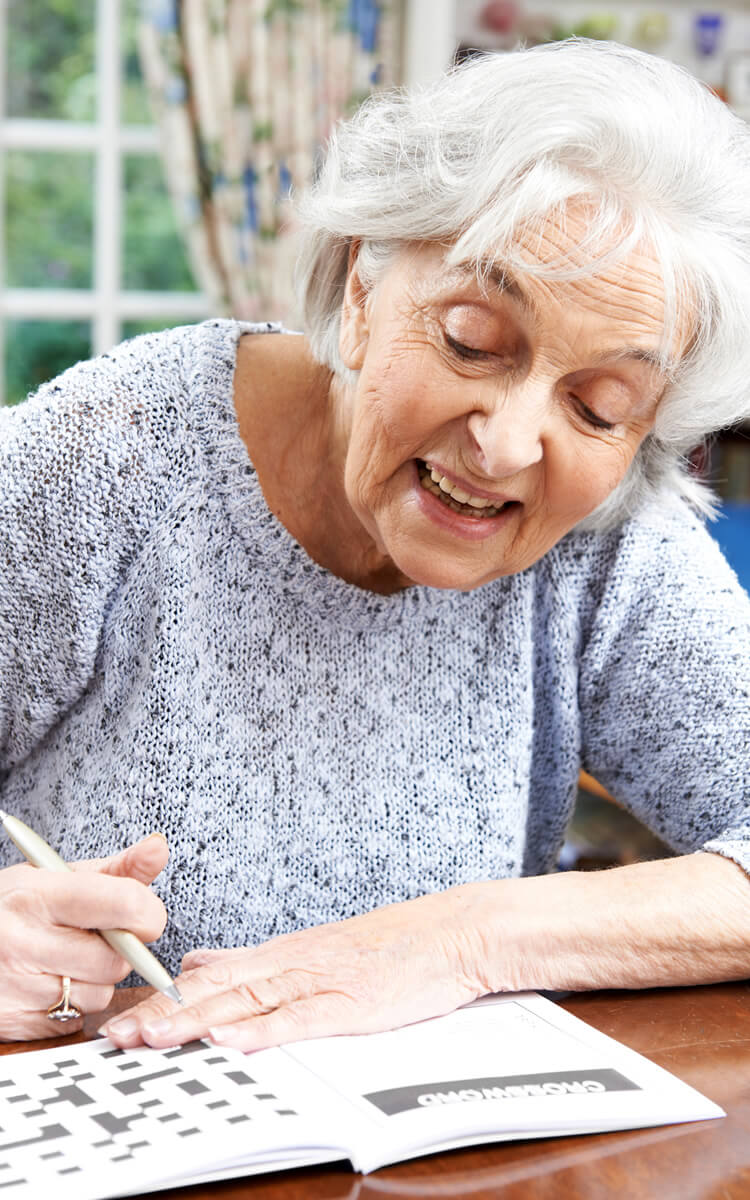 an elderly woman doing crossword puzzle for memory care