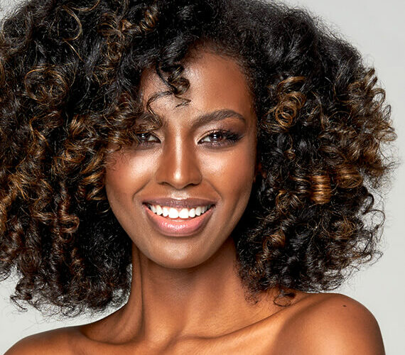 beautiful black woman smiling after using olaplex for curly hair