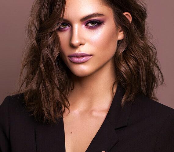 stylish brunette woman with wavy hair and black tuxedo jacket