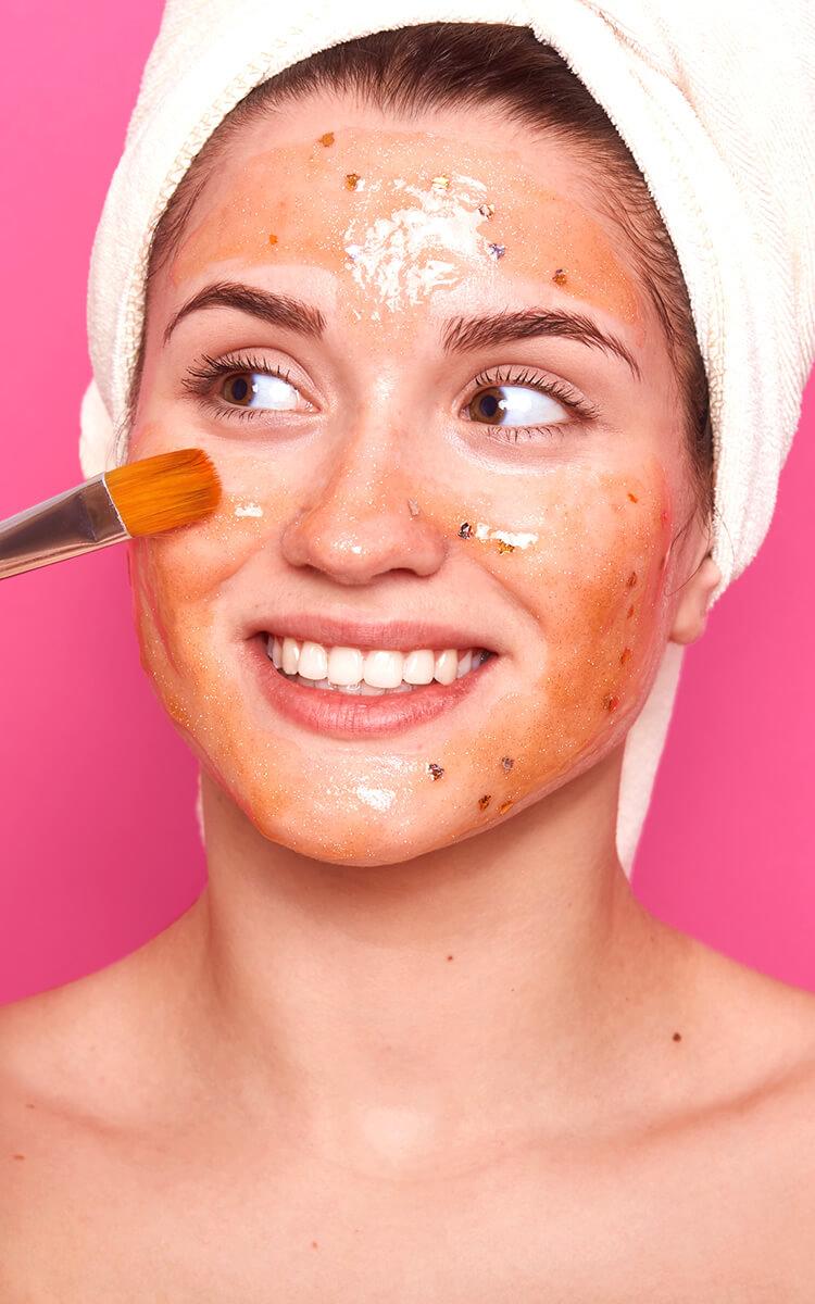 woman applying a tomato based facial mask
