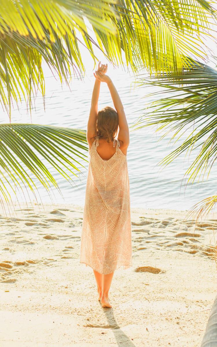 happy woman meditating on the beach under palms