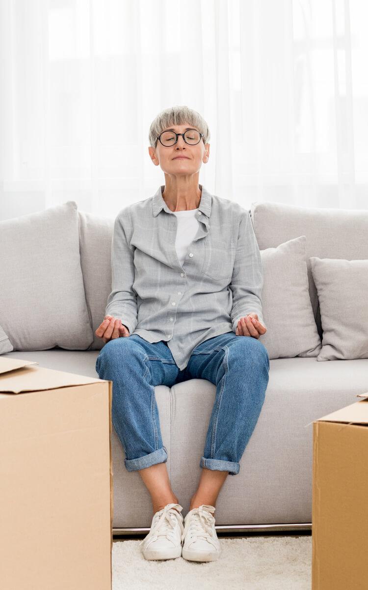 pretty mature woman meditating between boxes