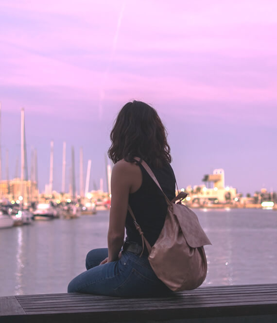pretty woman on a self journey sitting in a harbor