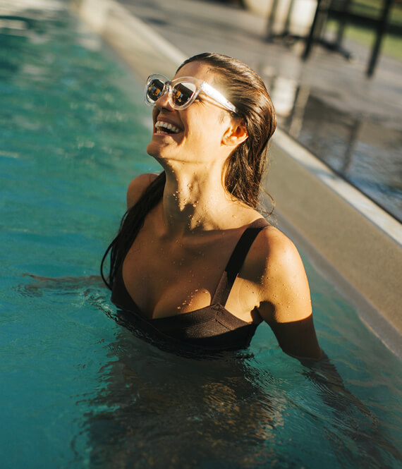 smiling laughing and happy woman swiming in sunlit pool