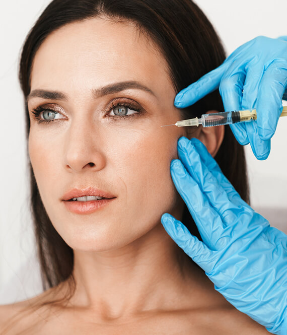 a woman gets botox injections for wrinkles on her face