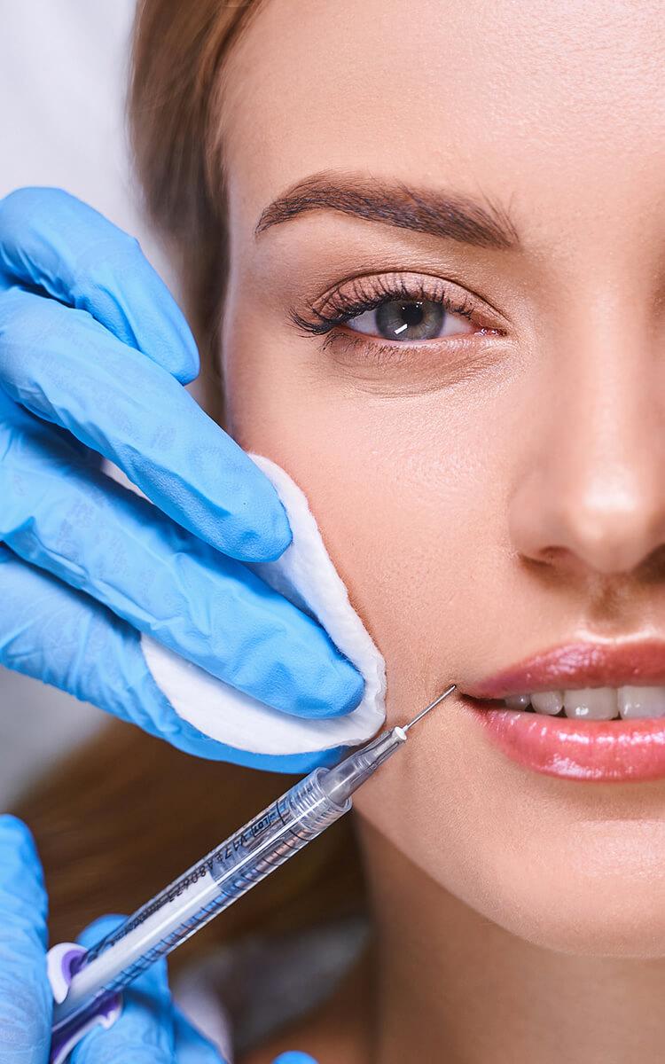 an estheatician injecting botox into womans face