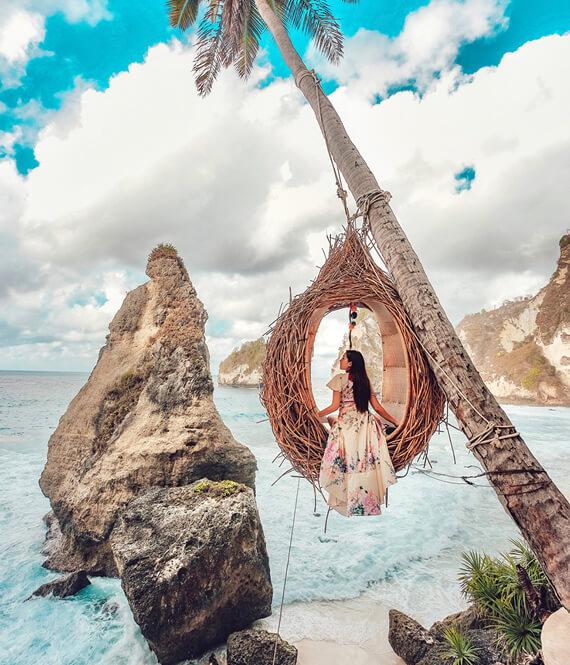 woman on a palm tree swing